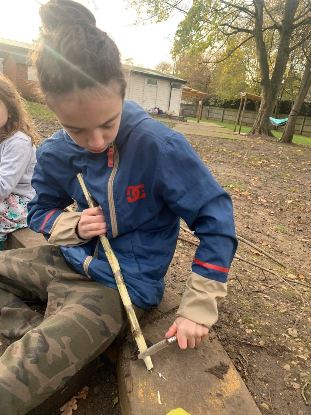 Child whittling wood outdoors